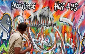 A man walks past graffiti about the euro zone debt crisis on a street in Lisbon